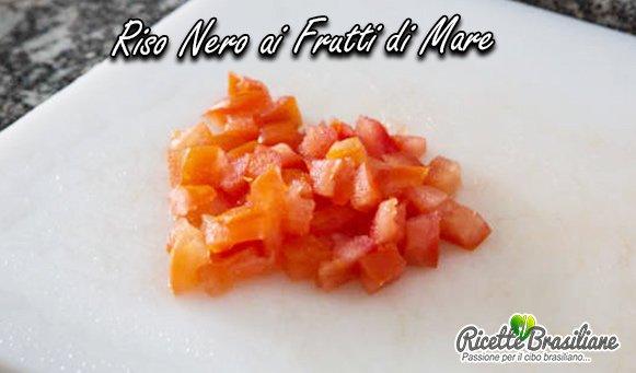 Taglia il pomodoro a cubetti. Condire i frutti di mare con sale e mettere da parte;